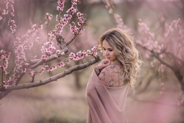 Retrato gentil de jovem loira encaracolada com saia pregueada marrom, blusa rosa e ombros cobertos com estola em jardins de pêssego em flor ao pôr do sol