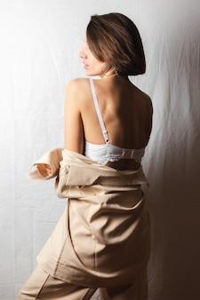 Retrato gentil de uma bela jovem com seios grandes em um terno bege e sutiã de renda branca em um branco acinzentado