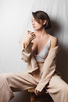 Retrato gentil de uma bela jovem com seios grandes em um terno bege e sutiã de renda branca sentada em uma cadeira em um branco cinza