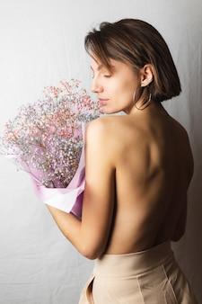 Retrato gentil de uma jovem em um pano branco em topless segurando um buquê de flores multicoloridas secas e sorrindo fofo, antecipação da primavera
