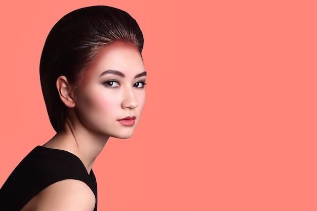 Retrato glamoroso de uma linda mulher asiática em um vestido preto sobre um fundo coral suave.