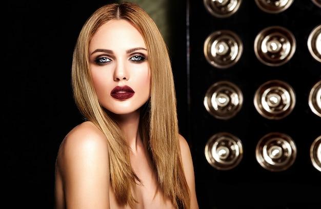 Retrato glamour sensual do modelo de mulher bonita com maquiagem diária fresca com lábios vermelhos escuros cor e rosto de pele limpa e saudável em luzes de estúdio