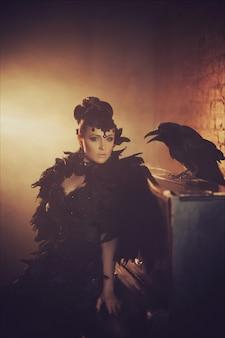 Retrato gótico da moda de uma bela morena com corvo em um vestido longo preto feito de penas de corvo. dia das bruxas