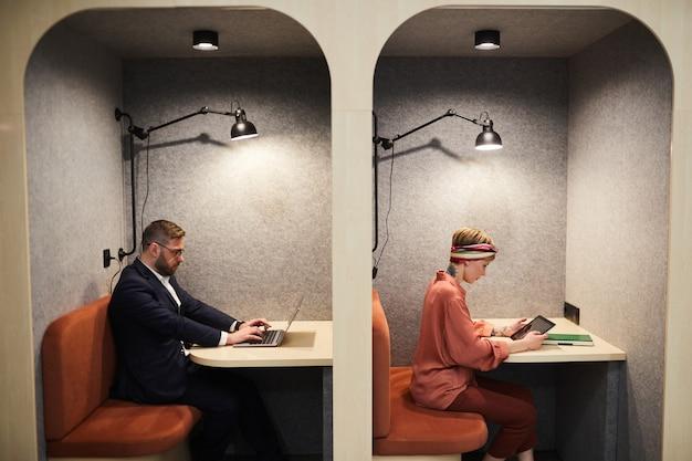 Retrato gráfico de vista lateral de dois empresários trabalhando em estandes separados no espaço de co-working, copie o espaço