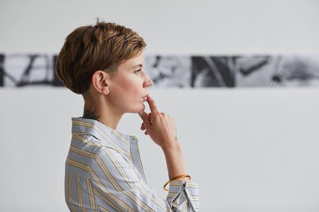 Retrato gráfico de vista lateral de uma jovem tatuada olhando pinturas em uma exposição de arte contemporânea,