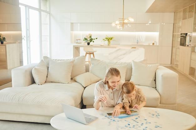 Retrato grande angular de duas irmãs resolvendo quebra-cabeças juntas enquanto desfrutam de um tempo dentro de casa em um interior branco