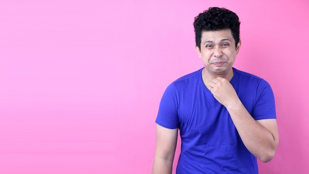 Retrato homem bonito da ásia há uma dor de garganta no fundo rosa no estúdio