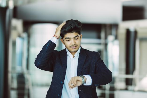 Retrato, homem negócios, observar, relógio, escritório