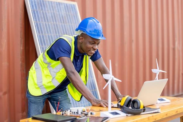 Retrato homem negro de engenharia segurando o recipiente do modelo do moinho de vento e a célula solar no fundo