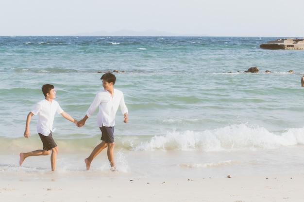 Retrato homossexual jovem casal asiático correndo juntos na praia.