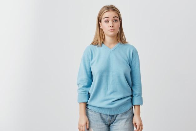 Retrato horizontal da atraente mulher de olhos escuros, vestida com suéter azul e calça jeans, parecendo espantada e chocada com as notícias que ela acabou de ouvir. menina bonita posando.