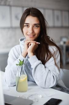 Retrato horizontal da bela jovem estudante, segurando a cabeça nas mãos enquanto está sentado no café, bebendo um coquetel, sorrindo para a câmera. mulher faz anotações no laptop, tirou os fones de ouvido para pedir algo.