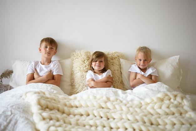 Retrato horizontal de adorável linda menina relaxando na cama entre seus dois irmãos idosos. irmãos crianças europeias charmosas cruzando os braços, recusando-se a acordar de manhã cedo