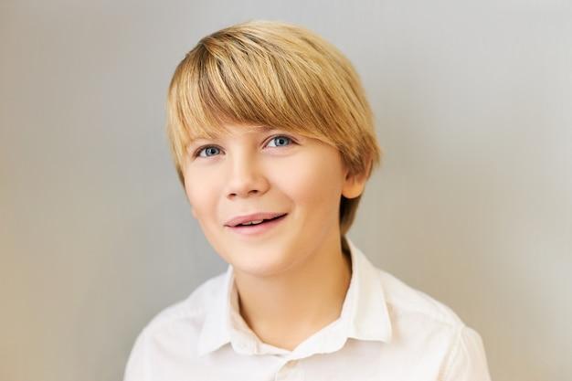 Retrato horizontal de atraente estudante caucasiano de olhos azuis com penteado elegante, sorrindo alegremente, tendo encantado a expressão facial animada, fascinado com algo incrível. emoções positivas