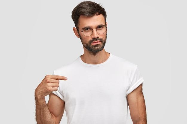 Retrato horizontal de bonito homem com barba por fazer e barba por fazer, vestido com uma camiseta branca casual, aponta para o espaço em branco da cópia para seu projeto, usa óculos. homem sério vendedor de roupas