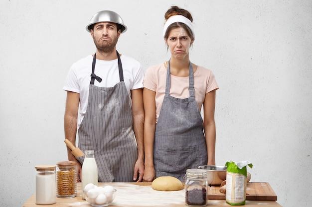 Retrato horizontal de cozinheiros talentosos e tristes curvando os lábios e olhando com expressão de descontentamento