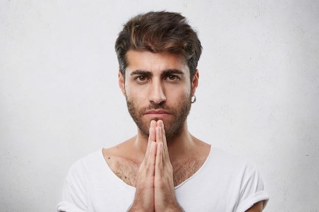Retrato horizontal de homem bonito com penteado da moda e barba usando brinco e camiseta branca, mantendo as mãos juntas rezando com os olhos cheios de fé para pedir algo melhor