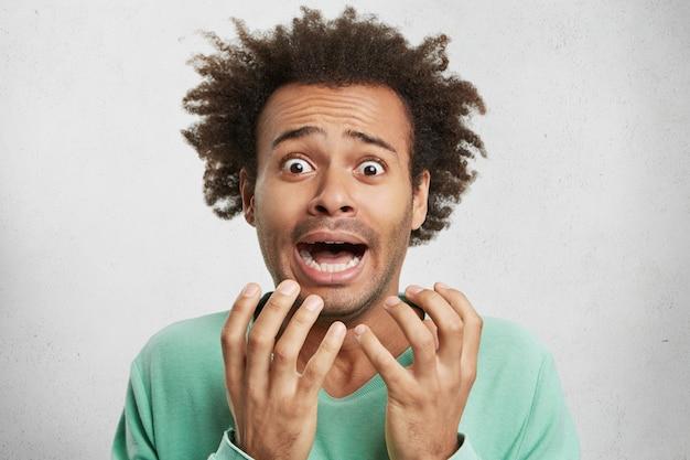 Retrato horizontal de homem mestiço e perplexo nervoso gesticula em pânico, tem expressões perturbadas e petrificadas