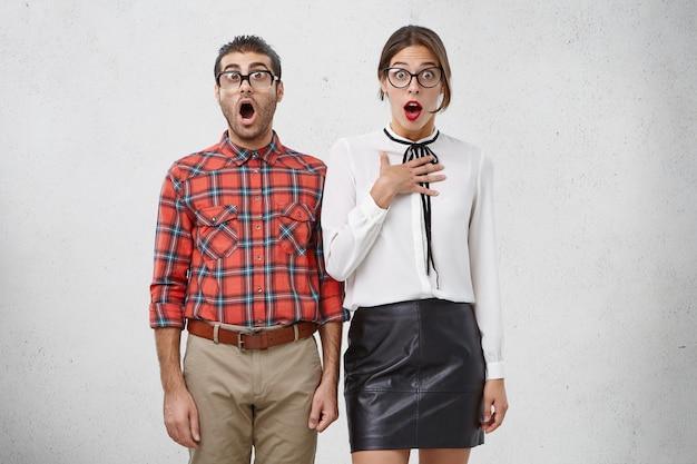 Retrato horizontal de homens e mulheres espertos em choque com a boca aberta