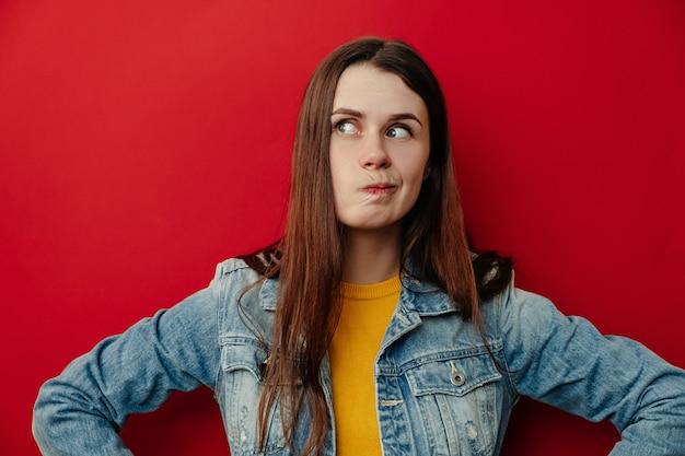 Retrato horizontal de jovem intrigado pensativo franze os lábios, pensa que decisão a tomar, usa jaqueta jeans, toma a decisão em mente, fica sobre fundo vermelho, com espaço em branco da cópia