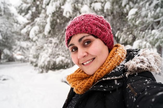 Retrato horizontal de jovem mulher caucasiana, sorrindo, respirando ar fresco ao ar livre, sob a neve.