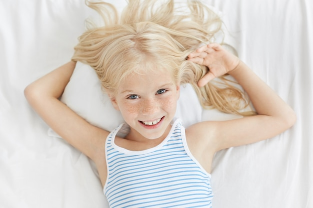 Retrato horizontal de linda garota com olhos azuis brilhantes, rosto sardento e sorriso gentil, relaxando na cama, deitado no travesseiro branco confortável
