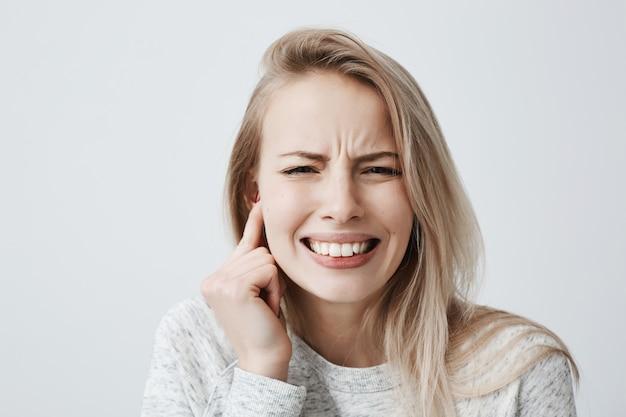 Retrato horizontal de loiro caucasiano feminino vestido casualmente tem dor de cabeça depois da festa barulhenta, aperta os dentes e segura a mão atrás da orelha. fêmea jovem irritada expressando emoções negativas.