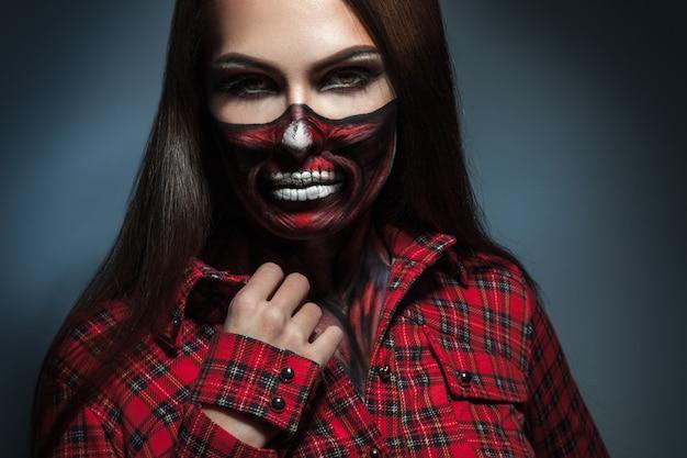 Retrato horizontal de menina adulta com arte de rosto assustador para a noite de halloween em estúdio