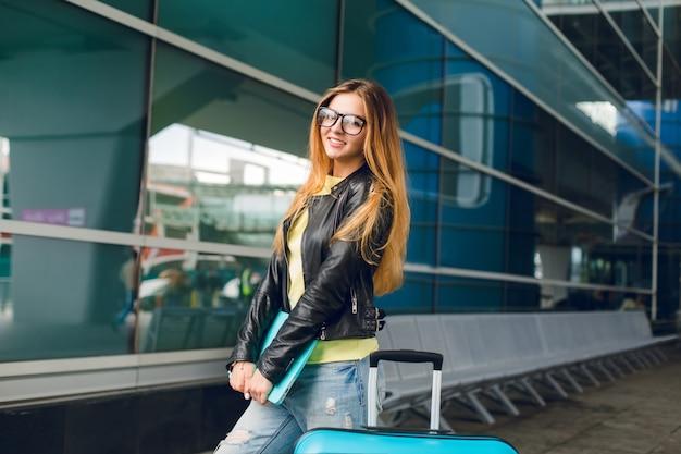 Retrato horizontal de menina bonita com cabelo comprido, do lado de fora no aeroporto. ela veste uma jaqueta preta com jeans., segura o laptop na mão. ela está sorrindo para a câmera.
