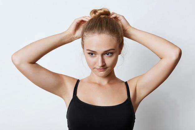 Retrato horizontal de mulher atraente com nó de cabelo loiro, olhando pensativamente para baixo com seus olhos azuis enquanto tenta fazer um coque, pensando em onde ir passear com os amigos. conceito de beleza