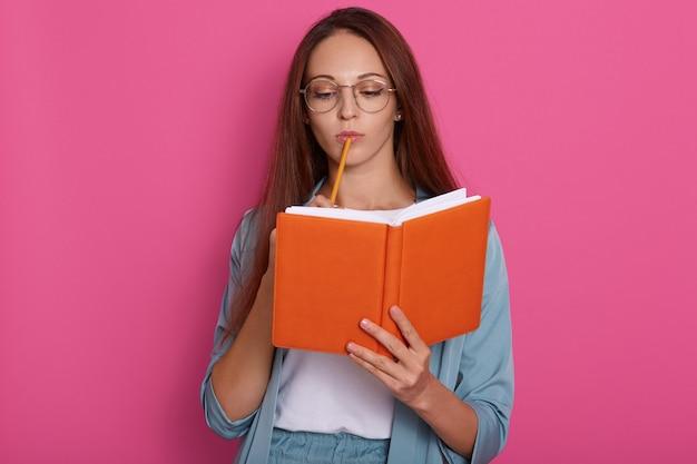 Retrato horizontal de mulher atraente pensativa com expressão facial pensativa, pensa sobre suas tarefas, planejando algo, vestindo terno