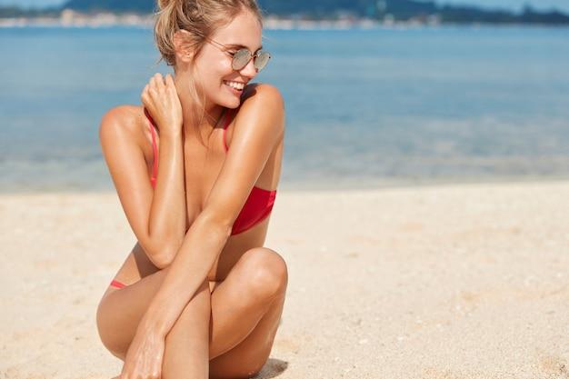 Retrato horizontal de mulher bonita e magra satisfeita com corpo em forma perfeita, pele bronzeada, usa óculos escuros e maiô, toma banho de sol perto do oceano, disposta a passar o lazer sozinha no litoral