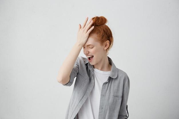 Retrato horizontal de mulher bonita ruiva com coque, tendo aberto a boca, segurando a mão na testa, tentando se lembrar de alguns detalhes.