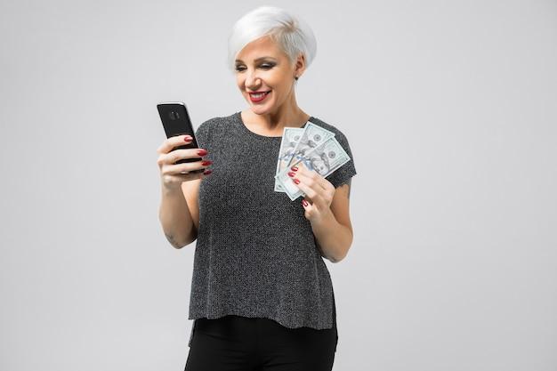 Retrato horizontal de mulher loira adulta com smartphone e lote de dinheiro
