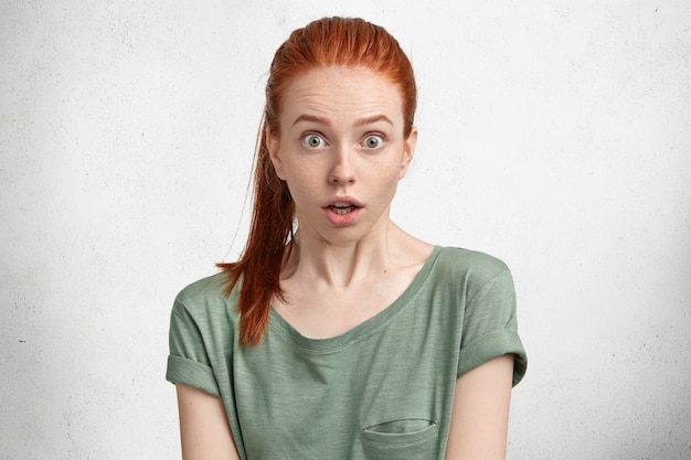 Retrato horizontal de mulher ruiva sardenta e beauitful atordoada em uma camiseta casual, prendendo a respiração
