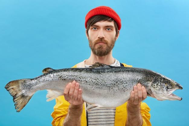 Retrato horizontal de pescador bem sucedido com barba segurando peixes enormes que ele pescou. jovem pescador vestido casualmente em pé com uma truta enorme. homem com capturas frescas. pesca e recreação