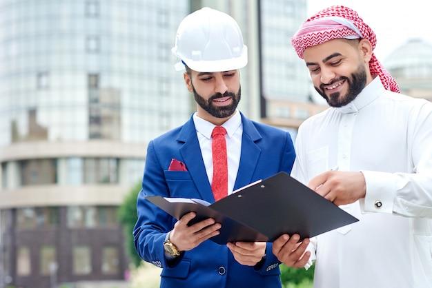 Retrato horizontal de um arquiteto assinando papéis em uma prancheta com seu cliente saudita