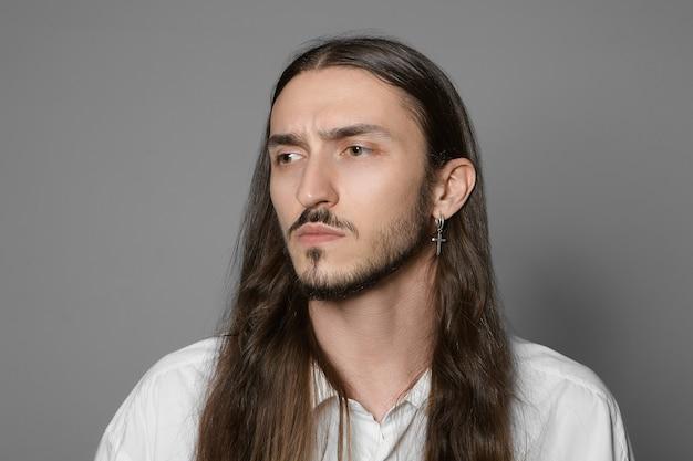 Retrato horizontal de um jovem elegante com a barba por fazer, brinco e penteado comprido e solto, sobrancelhas franzidas, preocupado com o trabalho, posando de camisa branca