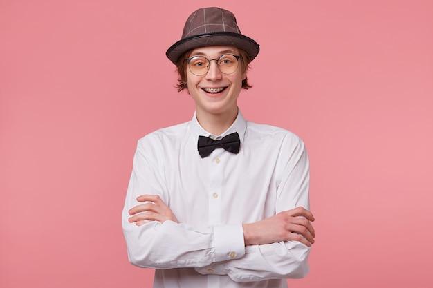 Retrato horizontal de um rapaz alegre e simpático com camisa branca, chapéu e gravata borboleta preta usa óculos sorrindo alegremente mostrando o aparelho, em pé com as mãos cruzadas, isolado no fundo rosa