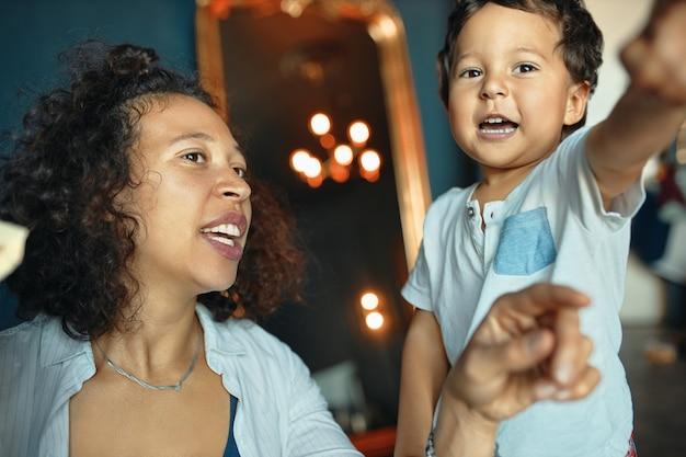 Retrato horizontal de uma bela jovem mestiça com cabelo encaracolado se divertindo dentro de casa com seu menino adorável e animado
