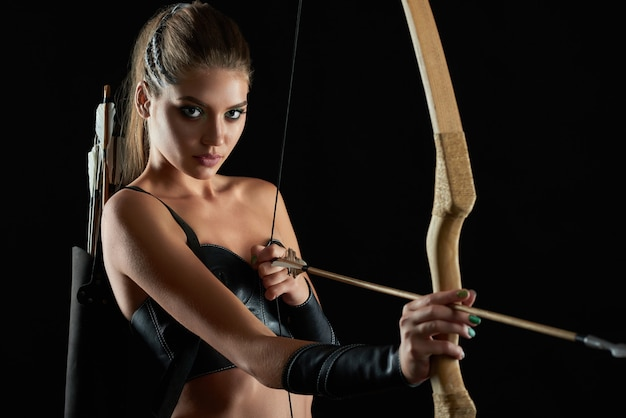 Retrato horizontal de uma deslumbrante jovem guerreira medieval sexy posando com um arco se preparando para atirar em seu inimigo com uma flecha no arco-e-flecha arqueiro de confiança de parede negra histórico.