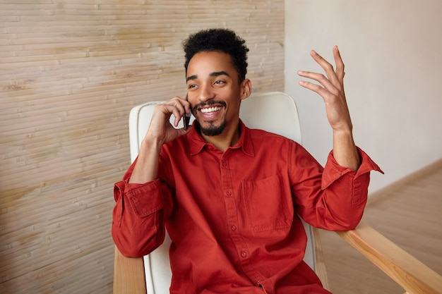 Retrato horizontal de uma jovem adorável feliz de pele escura com corte de cabelo curto, sorrindo alegremente enquanto conversa ao telefone e levanta emocionalmente a mão, sentado na cadeira no interior da casa
