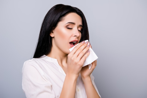 Retrato horizontal de uma jovem doente espirrando em um guardanapo