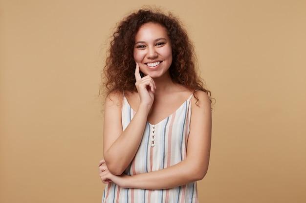 Retrato horizontal de uma jovem feliz encaracolada morena olhando alegremente com um largo sorriso e tocando seu rosto com a mão levantada, posando em bege