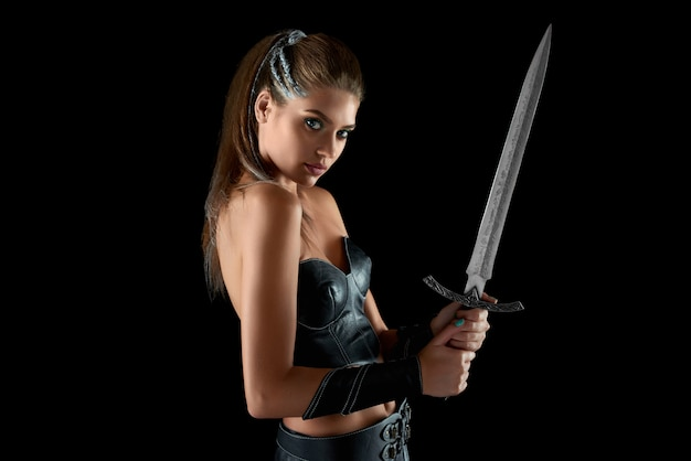 Retrato horizontal de uma jovem guerreira destemida posando com uma espada na parede preta lutadora de batalha bravura feminina feminilidade beleza coragem tribo amazonas.