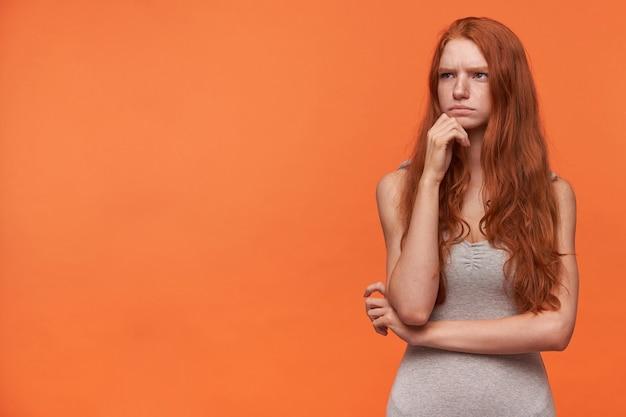 Retrato horizontal de uma jovem mulher bonita com cabelo ondulado de raposa olhando para o lado e carrancuda, tendo dúvidas em posar sobre um fundo laranja em uma camisa cinza casual