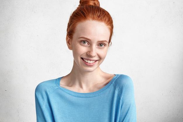 Retrato horizontal de uma linda mulher encantada com cabelos ruivos, sorriso largo e brilhante, vestida casualmente, expressa emoções positivas como alegria por ter um dia de folga, poses contra o branco