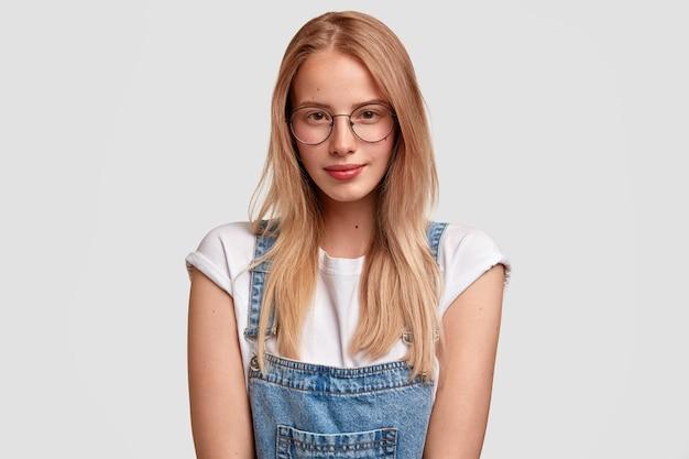 Retrato horizontal de uma mulher de aparência agradável em óculos e macacão jeans, pronta para ouvir palestras, se prepara para as aulas, em pé contra uma parede branca. conceito de pessoas, juventude e estilo
