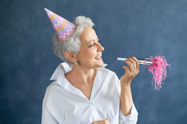Retrato horizontal de uma mulher de meia-idade bem-sucedida e confiante com uma camisa branca e um chapéu cônico brincalhão segurando o noisemaker