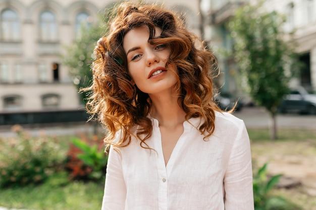 Retrato horizontal externo de mulher encaracolada elegante com cabelo ruivo posando e sorrindo em um bom dia de sol